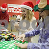 Rob Winner – rwinner@shawmedia.com<br /> <br /> (From front to back) Emma Carlson, 12, Breanna Hamrick, 12, and Travis Haak 13, all of Kirkland help wrap Christmas gifts during the Marine Corps Toys for Tots distribution event at the Salvation Army in DeKalb, Ill., Tuesday, Dec. 17, 2013.