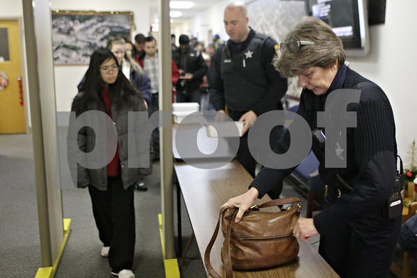 Rob Winner – rwinner@shawmedia.com<br /> <br /> Community service officer Pam Faivre (right) checks a purse as a line forms outside the courtroom on the second floor of the DeKalb Municipal Building on Monday, Dec. 16, 2013.