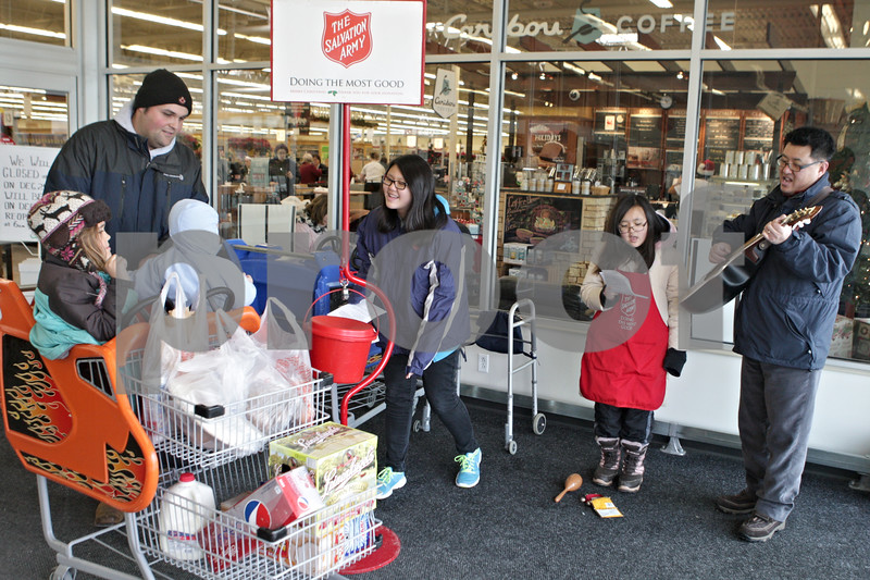 """Rob Winner – rwinner@shawmedia.com<br /> <br /> DeKalb resident Harley Siddall and his children Mia (left), 6, and Maddux, 1, drop money into a Salvation Army Red Kettle at the Hy-Vee in Sycamore as Captain Michael Cho (from right to left) plays guitar while singing """"O Holy Night"""" with his children Grace, 11, and Emily, 12, on Monday, Dec. 23, 2013."""