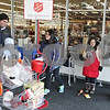"Rob Winner – rwinner@shawmedia.com<br /> <br /> DeKalb resident Harley Siddall and his children Mia (left), 6, and Maddux, 1, drop money into a Salvation Army Red Kettle at the Hy-Vee in Sycamore as Captain Michael Cho (from right to left) plays guitar while singing ""O Holy Night"" with his children Grace, 11, and Emily, 12, on Monday, Dec. 23, 2013."