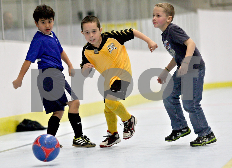 Monica Maschak - mmaschak@shawmedia.com<br /> From left: Aidan Camach, Michael Wiesner and Jimmy Ziegler go after the ball during a holiday soccer camp held at the Kishwaukee YMCA on Thursday, December 26, 2013. The camp serves children between first and third grade.