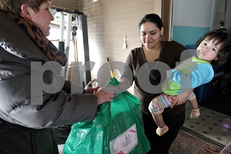 Monica Maschak - mmaschak@shawmedia.com<br /> Angelica Nava and her one-year-old daughter, Ingrid Dayana Arnulfonava, of DeKalb, accept a Christmas gift from volunteer Laura Frankiewicz during the Goodfellows gift distribution on Tuesday, December 24, 2013. About one hundred volunteers disbursed throughout the Sycamore and neighboring areas to give gifts to families in need.