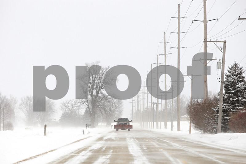 Rob Winner – rwinner@shawmedia.com<br /> <br /> A pick-up truck travels south on Somonauk Road near Shabbona Grove Road as snow drifts across the pavement in Squaw Grove Township on Thursday, Jan. 2, 2014.