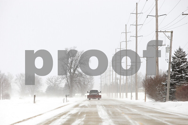 Rob Winner – rwinner@shawmedia.com<br /> <br /> A pick-up truck travels south on Somonauk Road near Shabbona Grove Road as snow drifts across the pavement in Squaw Grove Township on Thursday, Jan. 2, 2014.