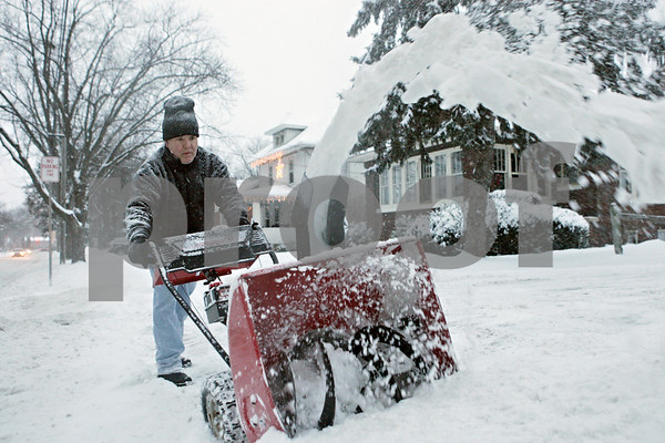 """Rob Winner – rwinner@shawmedia.com<br /> <br /> DeKalb resident Tim Schulz removes snow from his driveway with a snow blower on Wednesday, Jan. 1, 2014. """"Incidentally, I've found that listening to The Byrds is great music to remove snow to,"""" said Schulz."""