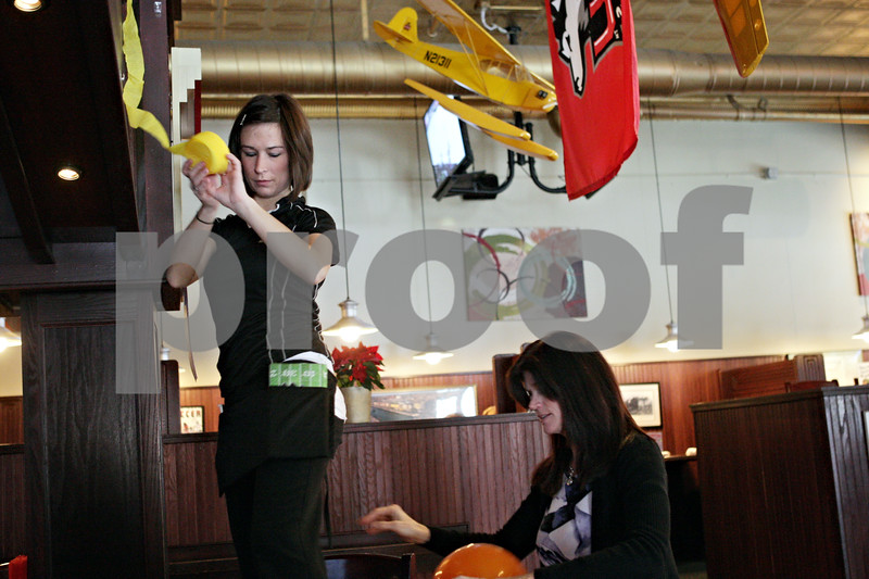 Rob Winner – rwinner@shawmedia.com<br /> <br /> Jeanann Sundby (left) and Debbie Witmer begin decorating O'Leary's Restaurant and Pub ahead of Tuesday night's New Year's party in DeKalb, Ill.