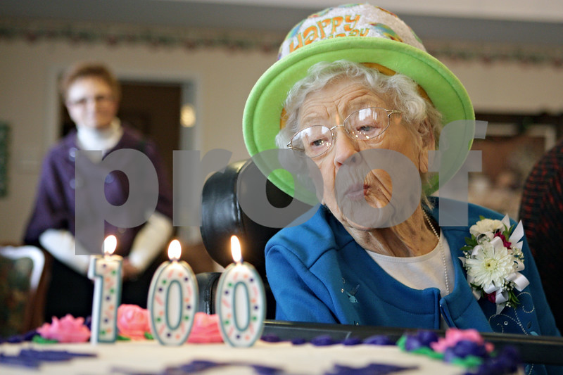 Rob Winner – rwinner@shawmedia.com<br /> <br /> Grand Victorian resident Marie McKenzie attempts to blow out the candles on her cake to celebrate her 100th birthday in Sycamore on Monday, Dec. 30, 2013. While McKenzie's birthday was actually on December 29, she celebrated with residents and staff on Monday afternoon.
