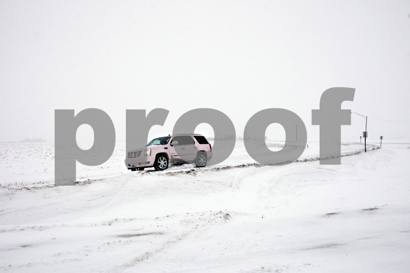 Rob Winner – rwinner@shawmedia.com<br /> <br /> A pink Cadillac Escalade merges onto Somonauk Road from Perry Road in Pierce Township as snow falls and covers the roads on Wednesday, Jan. 1, 2014.<br /> <br /> ***Do not run this for Thursday. I'd like it saved for the drifting snow story to run on Saturday. Also, feel free to add text to the white space. -Rob***