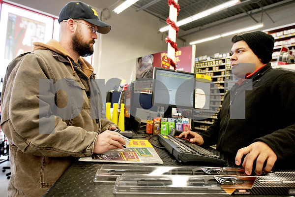 Monica Maschak - mmaschak@shawmedia.com<br /> Assistant Manager Dagoberto Andrade (right) rings up windshield wiper blades being purchased by Tom Corbett, of Genoa, for his van at Advanced Auto Parts in DeKalb on Friday, January 3, 2014. Due to the recent weather, Advanced Auto Parts has seen an increase in sales of wiper blades, windshield washer fluid and ice scrapers.