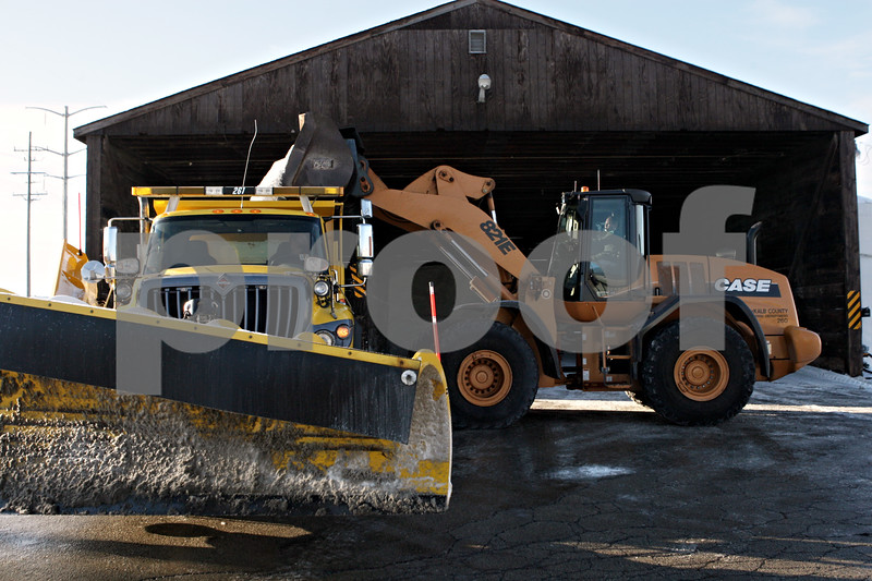Rob Winner – rwinner@shawmedia.com<br /> <br /> Driver Brian Koehnke (left) waits as his plow truck is filled with salt by a front end loader driven by Gene Capes at the DeKalb County Highway Department in DeKalb, Ill., Tuesday, Dec. 31, 2013.