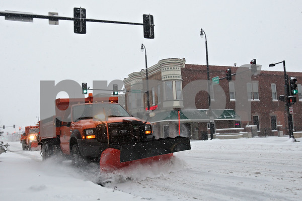 Rob Winner – rwinner@shawmedia.com<br /> <br /> A pair of snow plows remove snow from Lincoln Highway traveling west in downtown DeKalb on Wednesday afternoon.<br /> <br /> Wednesday, Jan. 1, 2014