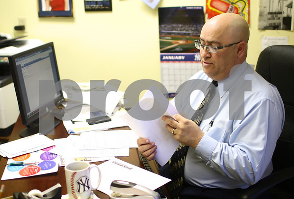 Kyle Bursaw – kbursaw@shawmedia.com<br /> <br /> John Saponari, the franchise general manager at Jackson Hewitt in DeKalb, pages through some documents while working on tax returns for clients Maria and Jose Secena on Thursday, Jan. 24, 2013.