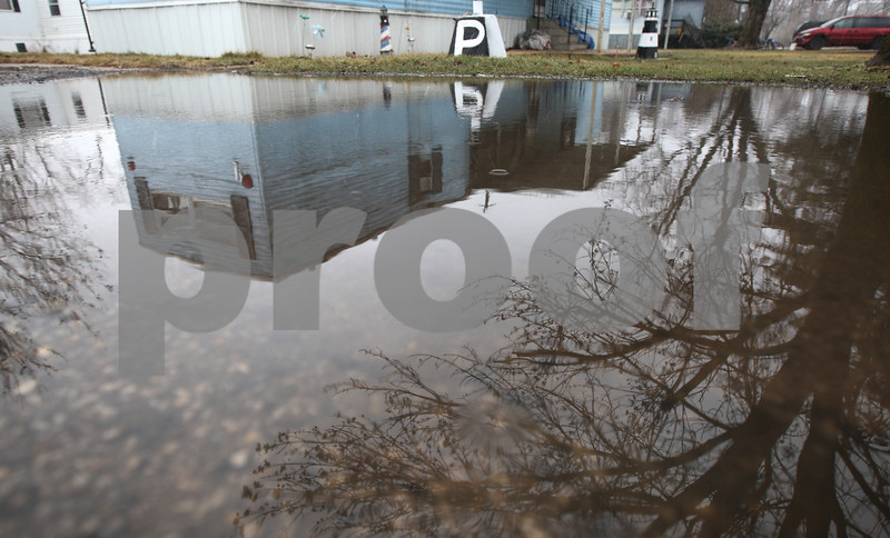 Kyle Bursaw – kbursaw@shawmedia.com<br /> <br /> A large puddle in the road reflects a trailer with a couple lighthouse lawn ornaments in front of it at Evergreen Village on Wednesday, Jan. 30, 2013.