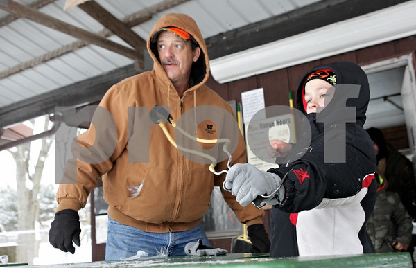 Rob Winner – rwinner@shawmedia.com<br /> <br /> Brian Wascher (left) watches as Ben Leverton, 9, of DeKalb Webelos I Pack 133 uses a slingshot to hit a target during the annual Klondike Derby held at Sycamore's Sportsman's Club in Sycamore, Ill., Saturday, Feb. 2, 2013.