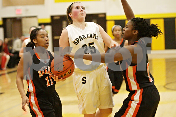 Rob Winner – rwinner@shawmedia.com<br /> <br /> Sycamore's Bailey Gilbert (25) draws a foul from DeKalb's Janay Wright (right) in the third quarter in Sycamore, Ill., Thursday, Feb. 7, 2013. DeKalb defeated Sycamore, 50-26.