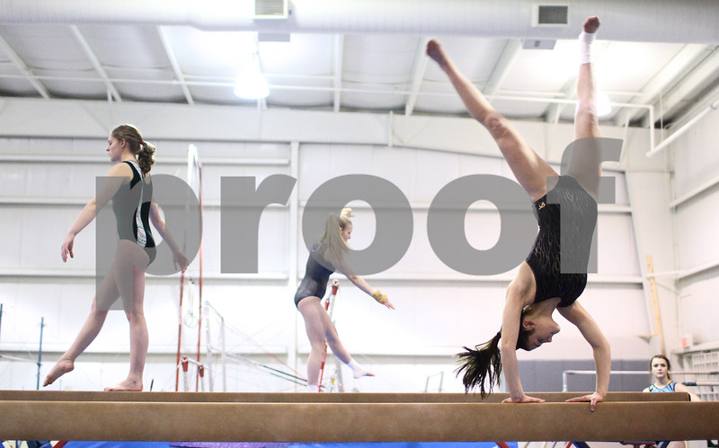 Kyle Bursaw – kbursaw@shawmedia.com<br /> <br /> Sycamore-DeKalb co-op gymnasts (from left) Emily Hartwig, Melissa Edmunds and Alison Morreale work on routines on the beam  works on a routine on the beam during practice at Energym on Friday, Feb. 1, 2013.