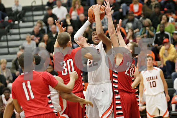 Rob Winner – rwinner@shawmedia.com<br /> <br /> DeKalb's Andre Harris (22) attempts a shot under the basket while being pressured by two Yorkville defenders during the fourth quarter in DeKalb, Ill., Friday, Feb. 15, 2013. Yorkville defeated DeKalb, 50-43.