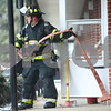 Kyle Bursaw – kbursaw@shawmedia.com<br /> <br /> A firefighter runs hose into the building at 921 Normal Road in DeKalb, Ill. where there was a fire on Monday, Feb. 11, 2013.
