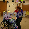 Jeff Engelhardt - jengelhardt@shawmedia.com<br /> Linda Dolder, a member of St. Catherine of Genoa, shows off her granddaughter to one of the Avancer residents during the church's Mardis Gras party Tuesday. Avancer serves special needs adults in an assisted-living community setting.