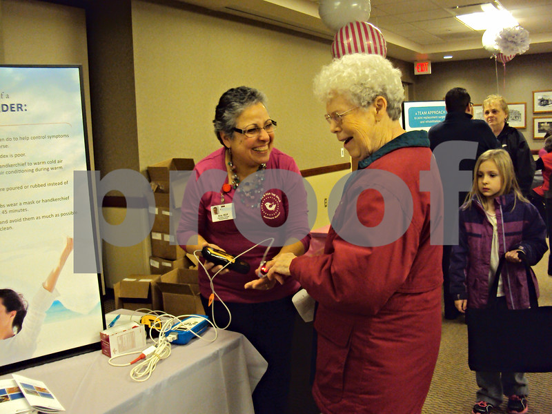 Lois Reed shares a laugh with respiratory therapist Ana Rondon-Thomas as she gets her blood oxygen level checked at Kishwaukee Community Hospital Friday.