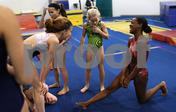 Kyle Bursaw – kbursaw@shawmedia.com<br /> <br /> DeKalb-Sycamore gymnast Anita Bell (right) is surrounded by some of the younger girls who practice at Energym as they debate the color of Bell's fingernails as she warms up for practice on Tuesday, Feb. 12, 2013.