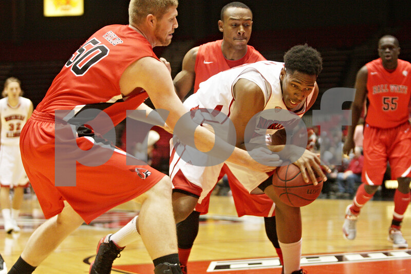 Rob Winner – rwinner@shawmedia.com<br /> <br /> Northern Illinois' Kevin Gray (right) attempts to regain control of a ball as Ball State's Zach Fields (50) reaches for it in the first half of their game in DeKalb, Ill., Wednesday, Feb. 13, 2013. Ball State defeated NIU, 56-52.