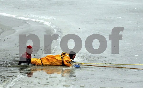 Firefighters Todd Adamson (left) and Andrew Romano (right)simulate an ice rescue Thursday at Rotary Park in DeKalb.<br /> (Stephanie Hickman - shickman@shawmedia.com)