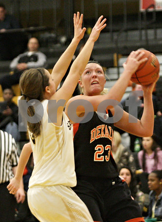 Rob Winner – rwinner@shawmedia.com<br /> <br /> DeKalb's Madelyne Johnson (23) looks to take a shot over Sycamore's Katherine Kohler (left) in the fourth quarter in Sycamore, Ill., Thursday, Feb. 7, 2013. DeKalb defeated Sycamore, 50-26.