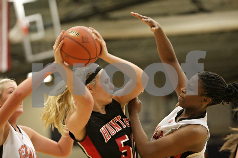 Rob Winner – rwinner@shawmedia.com<br /> <br /> Huntley's Ali Andrews (center) controls a defensive rebound between DeKalb's Madelyne Johnson (left) and Janay Wright in the fourth quarter during the Class 4A Belvidere North Regional semifinal in Belvidere, Ill., Tuesday, Feb. 12, 2013.