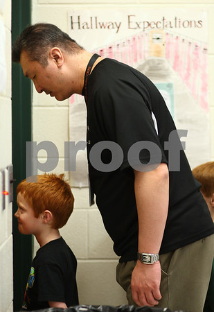 Kyle Bursaw – kbursaw@shawmedia.com<br /> <br /> Art teacher John Hahn jokingly stands behind Founders Elementary kindergarten student Bryan Chesser who was fixated on the classroom door's window while waiting for the classroom teacher to come and get the class from the art room on Tuesday, Jan. 29, 2013, Hahn's first day back to teaching after suffering a ruptured brain aneurysm on November 21, 2011.