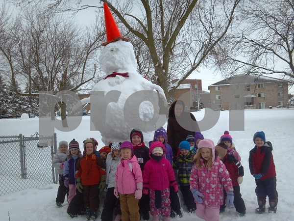 "From Rev. Marty Marks. Little Lambs preschool children with the giant snow man at Immanuel Lutheran church. The snowman was made by the college group ""Refuge"""