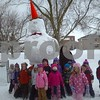 """From Rev. Marty Marks. Little Lambs preschool children with the giant snow man at Immanuel Lutheran church. The snowman was made by the college group """"Refuge"""""""