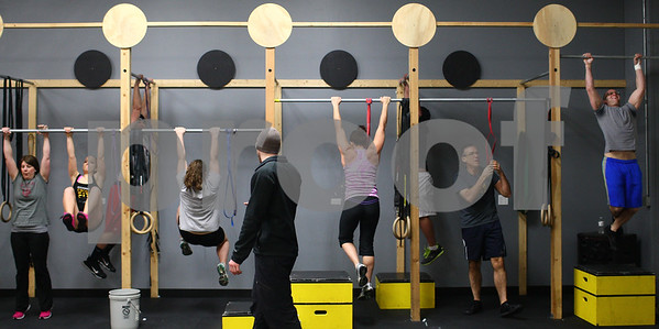Kyle Bursaw – kbursaw@shawmedia.com<br /> <br /> Mark Mitrovic (center, back to camera), co-owner of Sycamore CrossFit, encourages members as they do pull-ups or bring their knees up to their elbows during an evening workout on Monday, Feb. 18, 2013.