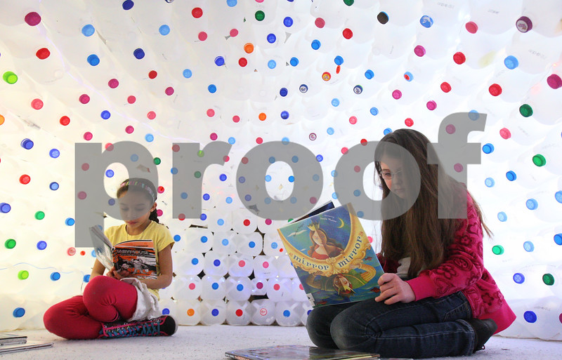 Kyle Bursaw – kbursaw@shawmedia.com<br /> <br /> South Prairie Elementary third-graders Milah Hopson (left) and Hope Orlowski read books inside of an igloo made of more than 400 empty milk containers during their class session in the school library in Sycamore, Ill. on Thursday, Feb. 14, 2013.