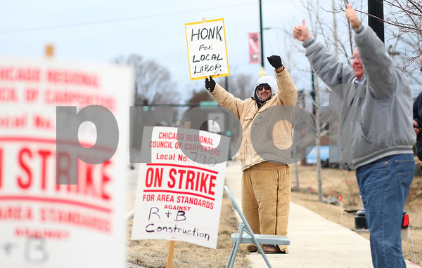 "Kyle Bursaw – kbursaw@shawmedia.com<br /> <br /> Richard Saenz (center) and Rick Lange (right), both of the DeKalb County Building Construction and Trades Council, respond to a vehicle that honked to show support on Monday, Feb. 18, 2013. Saenz, Lange and other workers were in front of the Hampton Inn and Suites Hotel construction site on S. Annie Glidden Road because they say the project was using a majority of out-of-state companies to do the work. ""It's a shame that [the hotel] didn't see fit to get local companies to do that work"" said Matt Swanson (not pictured), president of the DeKalb County Building and Construction Trades Council."