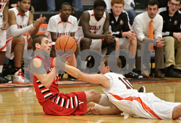 Rob Winner – rwinner@shawmedia.com<br /> <br /> Yorkville's Dakota Gette (left) tries to get a pass off from the floor as DeKalb's Pat Aves (10) reaches in during the second quarter in DeKalb, Ill., Friday, Feb. 15, 2013. Yorkville defeated DeKalb, 50-43.