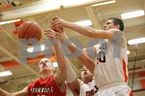 Rob Winner – rwinner@shawmedia.com<br /> <br /> Yorkville's Kyle Shimp (from left to right), DeKalb's Jake Smith and Jake Carpenter look to control a loose ball under the Barbs' basket during the first quarter in DeKalb, Ill., Friday, Feb. 15, 2013. Yorkville defeated DeKalb, 50-43.