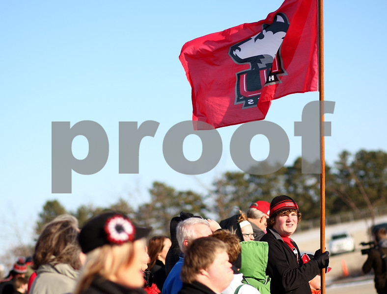 Kyle Bursaw – kbursaw@shawmedia.com<br /> <br /> Northern Illinois fans, including 16-year-old Clayton Kaus (with flag), line up on the curb in front of the Convocation Center to welcome back the Huskies to DeKalb on Wednesday, Jan. 2, 2013.
