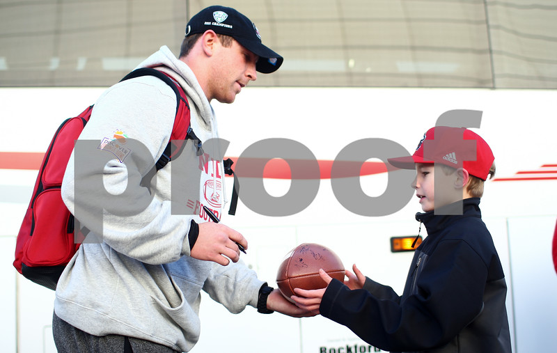Kyle Bursaw – kbursaw@shawmedia.com<br /> <br /> Northern Illinois quarterback Jordan Lynch returns a newly autographed football to 11-year-old Cole Heinisch, a DeKalb resident and NIU fan just outside of the Convocation Center as the team returned to DeKalb from their trip to Miami for the Orange Bowl on Wednesday, Jan. 2, 2013.