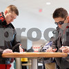"Erik Anderson - For the Daily Chronicle<br /> <br /> Northern Illinois University Graduate students (from left), Grzegorz Gadomski and Pawel Czajkowski, fill out a ""Student Expectation"" packet Sunday, December 30, 2012 at the Convocation Center in DeKalb, ILL."