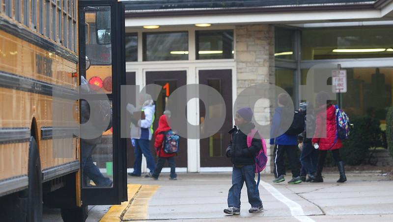 Kyle Bursaw – kbursaw@shawmedia.com<br /> <br /> Bresiess Marquez (center) finds a bus after school at Founders Elementary on Thursday, Jan. 10, 2013.