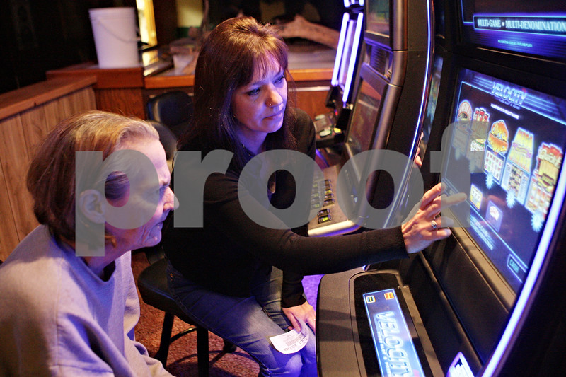 Rob Winner – rwinner@shawmedia.com<br /> <br /> Kingston resident Brenda Atkinson (left) is helped by bartender Brandy Miller while playing one of the three video gambling machines at Karlsbad Tavern in Genoa, Ill., Wednesday, Jan. 9, 2013.