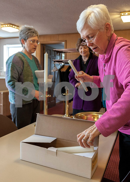Erik Anderson - For the Daily Chronicle<br /> <br /> Trustee Phyllis Roush changes a set of candles while Deacon Diana Swanson (left) and Sunday School Coordinator Jan Wylde talk Sunday, January 6, 2013 at the re-opening of the Mayfield Congregational Church in Mayfield. The churches roof collapsed nine months ago and after a renovation, re-opened for it's Sunday service.