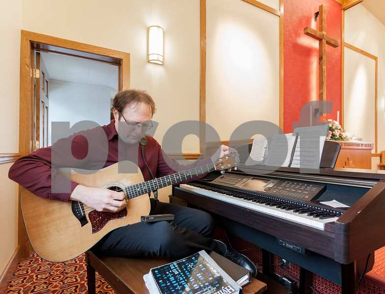 Erik Anderson - For the Daily Chronicle<br /> <br /> Music Director Chris Pawola tunes his guitar before the choir sings for service Sunday, January 6, 2013 at the re-opening of the Mayfield Congregational Church in Mayfield.