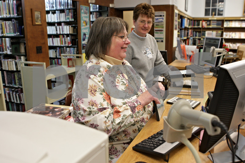 Rob Winner – rwinner@shawmedia.com<br /> <br /> Assistant librarian Lisa Muldowney (front) checks in items while talking with librarian Janet Sutter at the Sandwich Public Library on Wednesday, Jan. 2, 2013. The library received $1.6 million from the state and passed a referendum to issue $3.4 million in bonds. The current building was built in 1941 and in desperate need of an upgrade as it is only 4,780 square feet and is holding more than double the materials than it was built for.