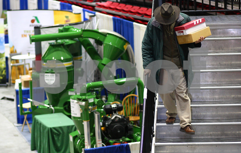 Kyle Bursaw – kbursaw@shawmedia.com<br /> <br /> A man brings a few boxes down the stairs in the Convocation Center during the set up day for the Northern Illinois Farm Show on Tuesday, Jan. 8, 2013.