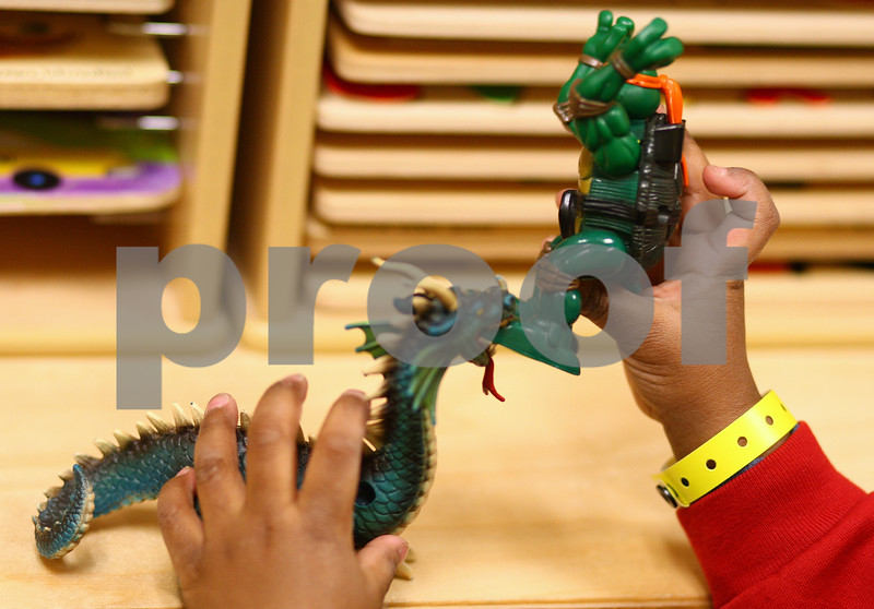 Kyle Bursaw – kbursaw@shawmedia.com<br /> <br /> A child plays with a Teenage Mutant Ninja Turtle and a dragon toy in the children's waiting room at the DeKalb County Courthouse in Sycamore, Ill. on Tuesday, Jan. 15, 2013.