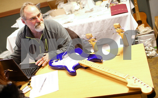Kyle Bursaw – kbursaw@shawmedia.com<br /> <br /> Tom Fuller, of the Collectors and Modern Electronics Roadshow, looks up values for two Ibanez bass guitars and a Squier guitar being sold by Amy Speweik of Elgin on Thursday, Jan. 17, 2013. Fuller paid $156 in cash to Speweik for the three items. The show, held in the Best Western at 1212 Lincoln Highway will continue buying from 9 a.m. to 6 p.m. Friday and Saturday.
