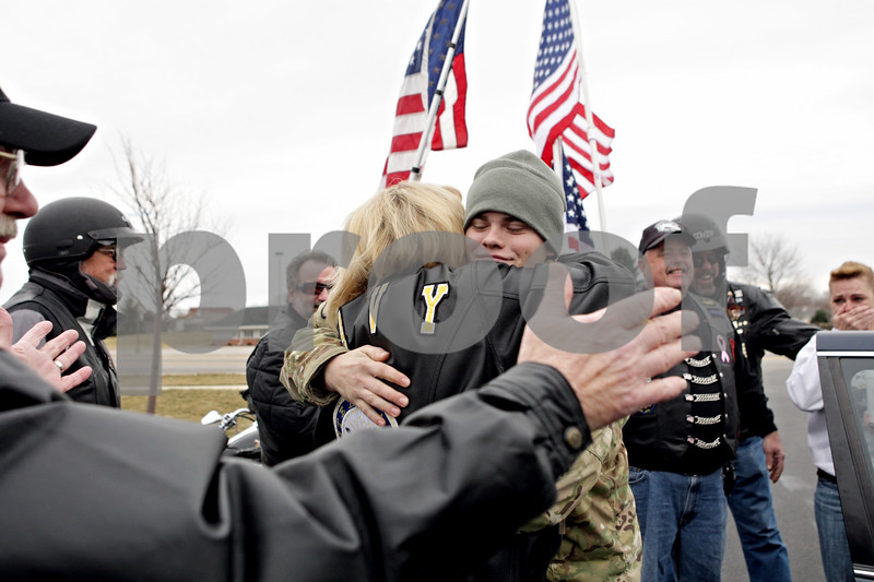 Rob Winner – rwinner@shawmedia.com<br /> <br /> Army Pfc. Craig Everhart (center) is welcomed home by a group of Warriors' Watch Riders as well as local fire and law enforcement outside the Sugar Grove Fire Department on Saturday, Jan. 12, 2013. Everhart is a 2009 Hinckley-Big Rock graduate and served nine months in Afghanistan during 2012.