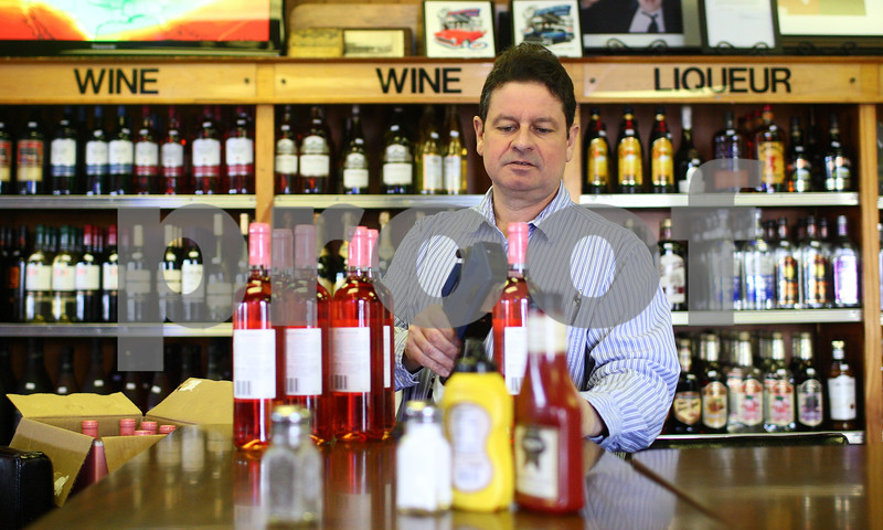 Kyle Bursaw – kbursaw@shawmedia.com<br /> <br /> Earl Sullivan, co-owner of Sullivan's Tavern, puts prices on product while stocking the liquor shelves in the DeKalb establishment which is a bar, restaurant and liquor store on Wednesday, Jan. 16, 2013.